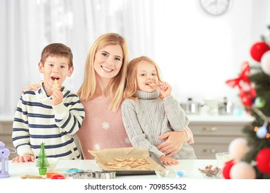 Young woman preparing Christmas cookies with little children in kitchen