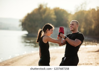 Young woman is preparing for fight with her trainer outdoors
