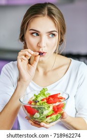 A young woman is preparing food in the kitchen. Copy space. The concept is healthy food, diet, vegetarianism, weight loss.