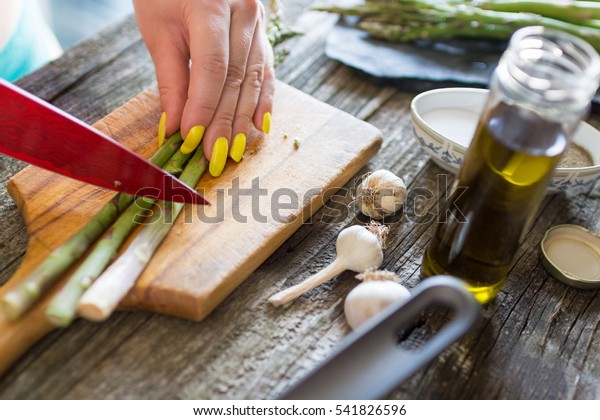 Young woman preparing healthy meal with asparagus on a cutting board