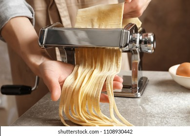 Young woman preparing noodles with pasta maker at table