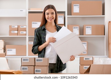 Young woman preparing parcel envelope for shipment to client in home office