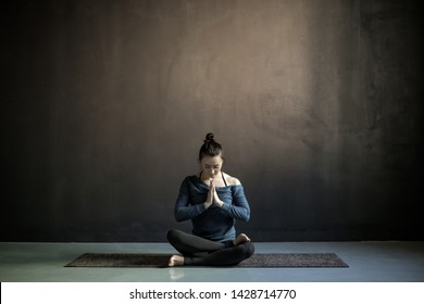 Young woman preparing to practice yoga, sitting on meditation session. Full length. Studio black wall with copyspace