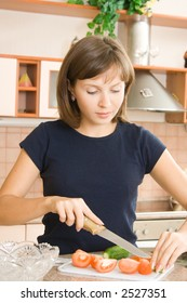 A young woman preparing salad in the kitchen