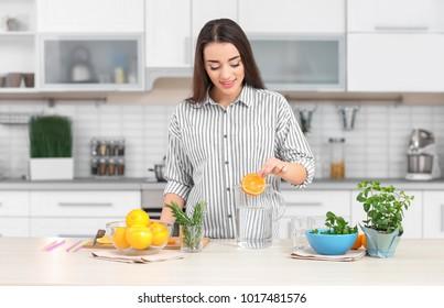Young woman preparing tasty lemonade in kitchen