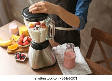 Young woman preparing yogurt smoothie with berries and fruits on table in the kitchen