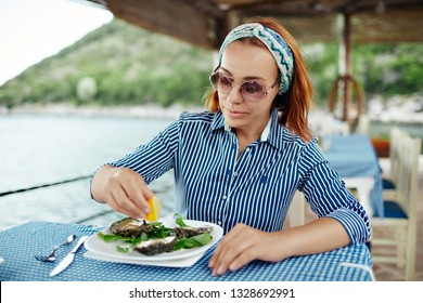 Young woman presses lemon juice on an oyster. Beautiful young woman eating seafood in an outdoor restaurant
