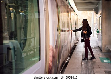 young woman pressing the door button to open the door and board the streetcar, concept of public transportation and urban lifestyle