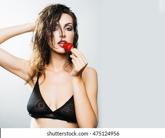 young woman with pretty face and wet hair in black bra holding red strawberry berry fruit in studio on grey background, copy space
