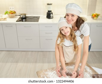 Young woman and pretty girl making heart shaped cookies with chokolate dough on pastry board. Mother and child in white and brown aprons and chef hats posing at camera, smiling.