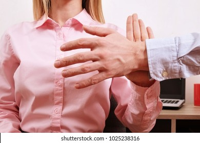 Young woman prevents man from groping her breast. #Metoo movement. Me too. Strong female stands up to male. Hostile work environment. Anti sexism protest against inappropriate behavior towards women