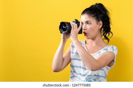 Young woman with a professional digital SLR camera on a yellow background