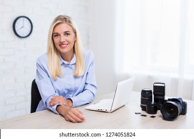 young woman professional photographer with camera, computer and photography equipment working in modern office