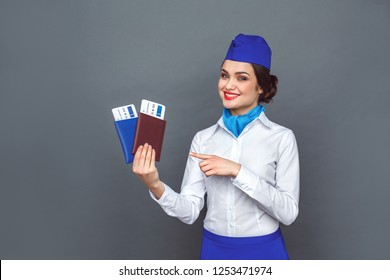 Young woman professional stewardess standing isolated on grey wall pointing at passports and plane tickets looking camera smiling toothy