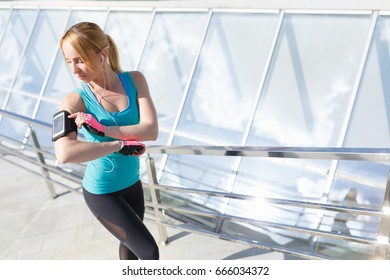 Young woman programming her mobile before going jogging to track performance. Running concept
