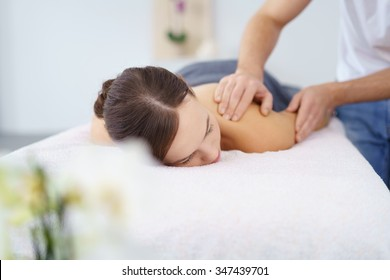 Young Woman in Prone Position Having a Massage in her Upper Back by her Physical Therapist.