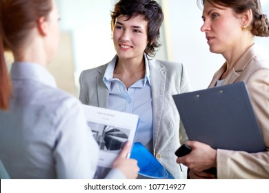 Young woman pronouncing business ideas, her colleagues listening to her with attention