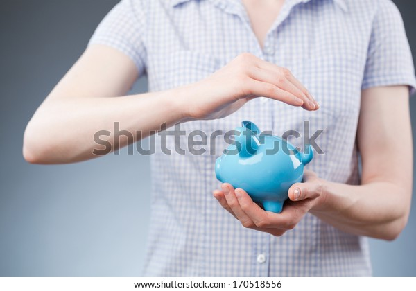 A young woman protecting a piggy bank with her hands - concept about safe deposits, savings or financial future.
