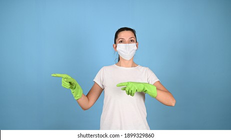 Young woman in protective face mask and green gloves pointing at something on blue. Young brunette on color background with coy space. Commercial cleaning company concept. . High quality photo