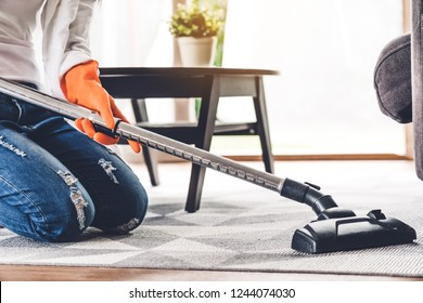 Young woman in protective gloves cleaning home with vacuum cleaner in living room at home