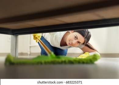 young woman in protective gloves cleaning floor under bed with mop