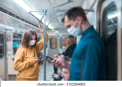 young woman in a protective mask standing in a subway car.