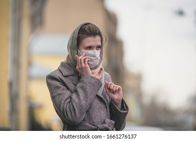 Young woman in a protective mask talking on a smartphone on the street