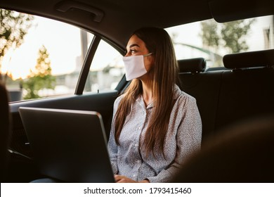 Young woman with protective mask working in a car