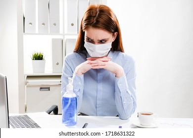 A young woman in a protective mask works on a computer. Business woman at the desk.