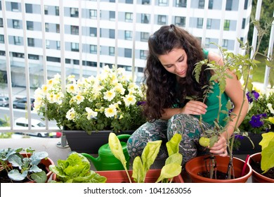 Young woman proud of her small kitchen garden in pots on her balcony in the city