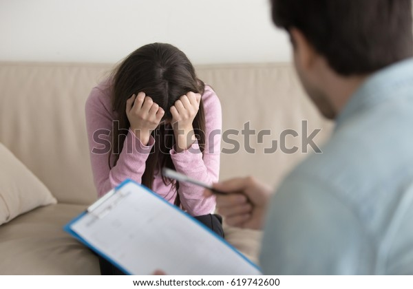 Young woman at the psychologist, feeling hopeless and depressed, crying holding her head in hands, upset teenage girl just found out about unwilling pregnancy or having disease