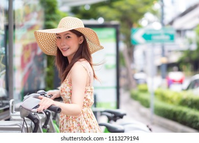Young woman with public sharing bicycle in city