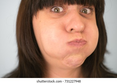 Young woman puffed her cheeks and held her breath.