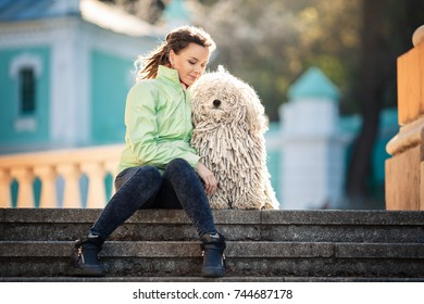 Young woman with puli dog sitting at the street. City. Lifestyle.