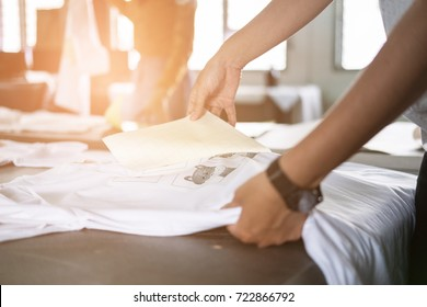 Young woman pull out paper from waterproof film on fabric. worker working on manual screen printing on t-shirt at her shop.