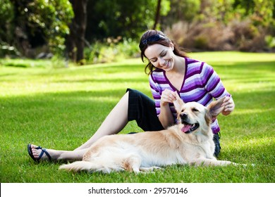 Young woman pulling ears of golden retriever in the park