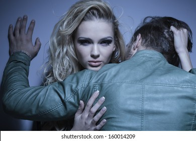 young woman is pulling her boyfriend to her by his hair, man standing with his back at the camera while embracing his lover
