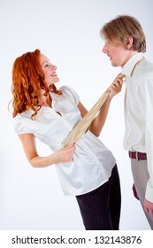Young woman pulling man by tie in studio on white background