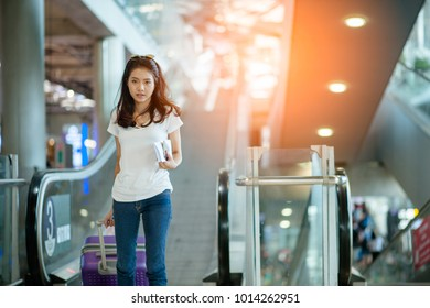 Young woman pulling suitcase in modern airport terminal. Travelling guy with his luggage while waiting for transport. Rear view. Copy space