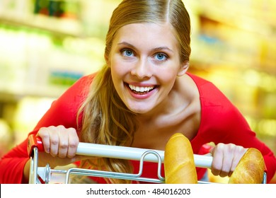 A young woman pulling a trolley, looking at camera and smiling