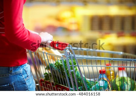 A young woman pulling a trolley with provision along the grocery
