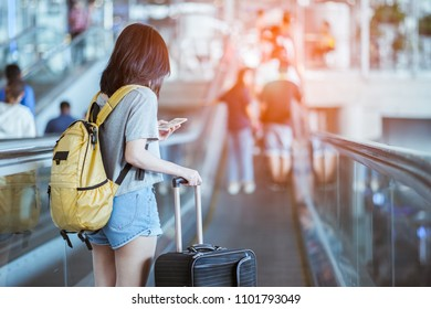 Young woman pulling and use smartphone suitcase in modern airport terminal. Travelling guy with his luggage while waiting for transport. Rear view. Copy space