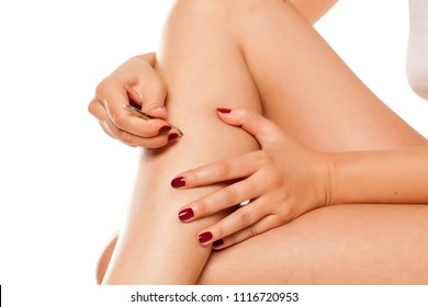 young woman pulls out the hairs on her legs with tweezers on white background