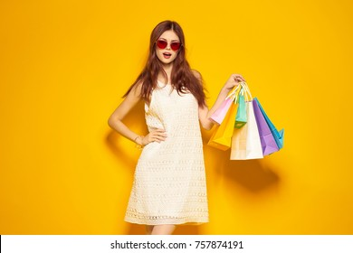 young woman with purchases on a yellow background, fashion, beauty