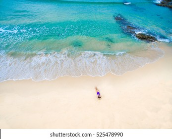 Young woman in a purple bikini lying on the sand near turquoise sea. Top view. Surin beach, Phuket, Thailand. Aerial Shooting.