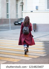 young woman in purple coat with black backpack cross the street crosswalk, rear view
