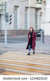 young woman in purple coat with coffee cup cross the street crosswalk, vertical photo