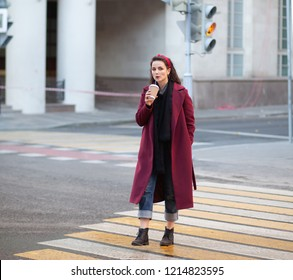 young woman in purple coat and drinking coffee cup cross the street crosswalk