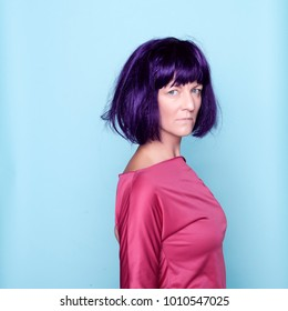 Young woman with purple wig on blue background in studio