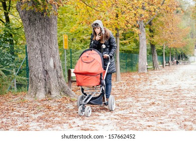 Young woman pushing her baby in stroller in a park